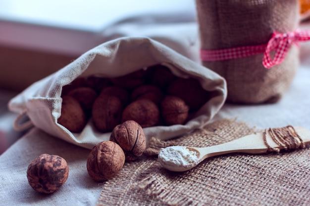 Nüsse in einem sack und einem löffel mit mehl