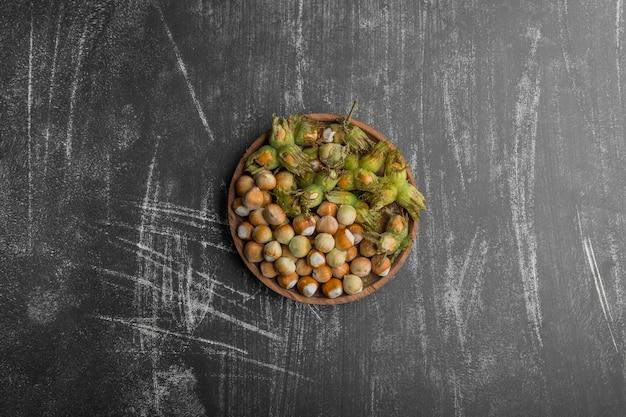 Nüsse in grünen muscheln in einer holzplatte in der mitte
