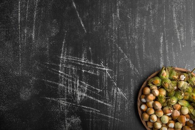 Nüsse in muscheln mit grünen blättern in der unteren ecke
