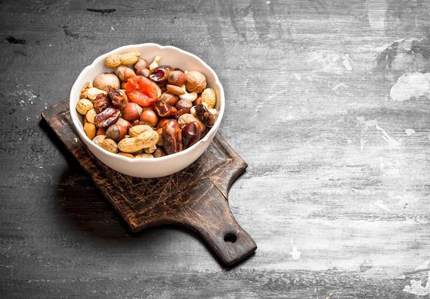 Nüsse mit getrockneten früchten in einer schüssel auf einer schwarzen tafel