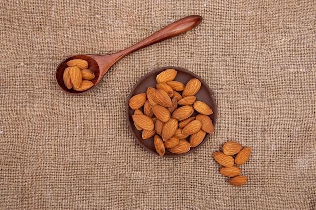 Nüsse pistazien in einem holzlöffel und einem braunen steingut teller auf alten sackleinen
