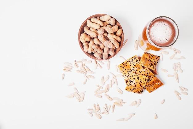 Nüsse und cracker mit bier auf weiß.