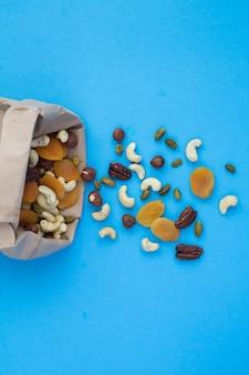 Nüsse und getrocknete aprikosen in einer papiertüte