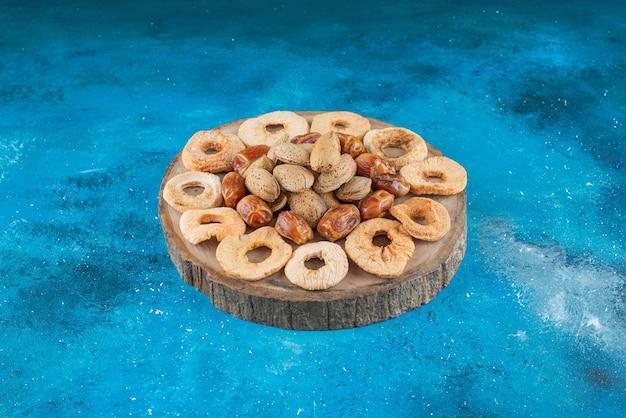 Nüsse und getrocknete früchte auf einem brett auf der blauen oberfläche
