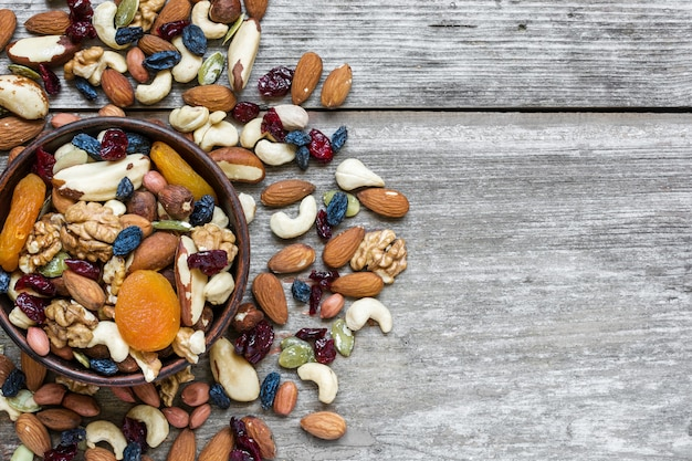 Nüsse und getrocknete früchte in einer schüssel über rustikalem holztisch