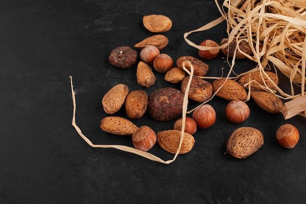 Nüsse und trockene früchte auf schwarzer oberfläche.
