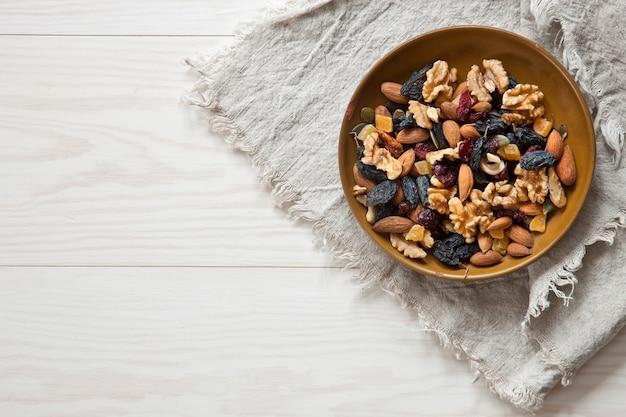 Nüsse und trockenfrüchte auf weißem hölzernem hintergrund. draufsicht, nahaufnahme. herbst-konzept