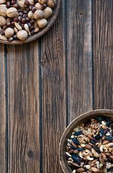Nüsse und trockenfrüchte in der hölzernen schüssel auf rustikalem hölzernem hintergrund.