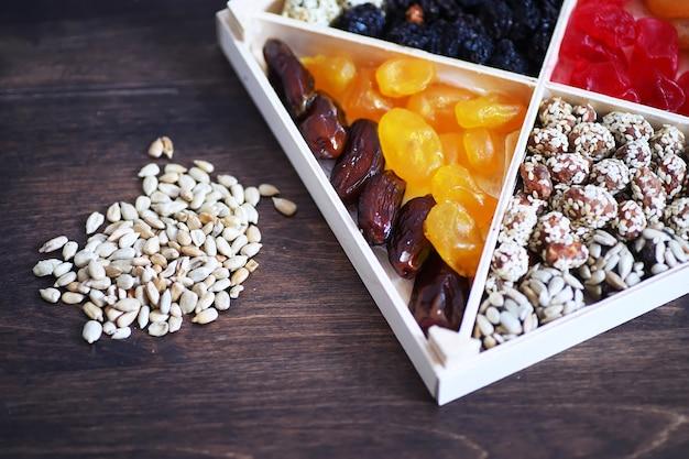 Nüsse und trockenfrüchte-sortiment auf steintisch-draufsicht.