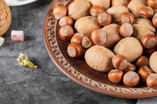 Nüsse und walnüsse in einer dekorativen platte auf einem stück marmor