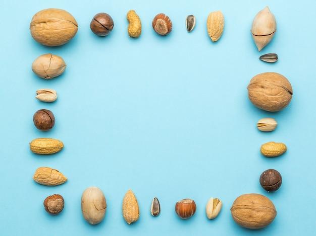 Nüsse verschiedener sorten in form eines rahmens auf blau. vegetarisches essen.