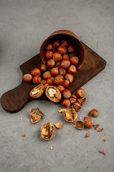 Nüsse, walnüsse und haselnüsse in einem braunen topf auf einem grau verteilen