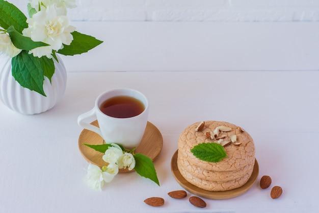Nützliche fastenzeitplätzchen aus mandelmehl gestapelt auf weißem holzhintergrund mit tasse jasmintee. selektiver fokus