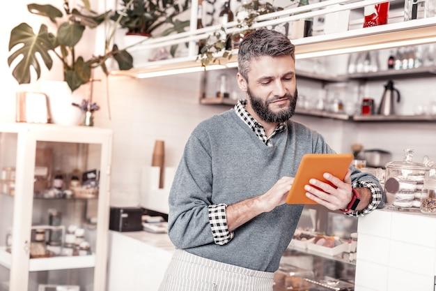 Nützliche informationen. erfreuter netter mann, der eine tafel hält, während er einen interessanten artikel darüber liest