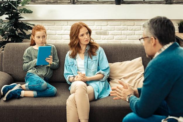 Nützliche informationen. schöne ernsthafte frau, die auf dem sofa sitzt, während sie den ratschlägen des psychologen über ihre tochter zuhört