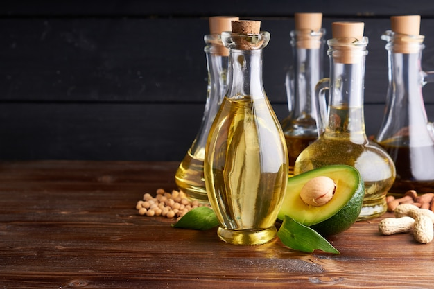 Nützliche pflanzenöle in glasflaschen. avocadoöl, kichererbsenöl, leinöl, erdnussöl, mandelöl.