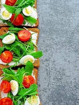 Nützliche und leckere fitness-toasts mit rucola, frischkäse, kirschtomaten und wachteleiern. das konzept eines richtigen snacks. weizentoast mit salat.