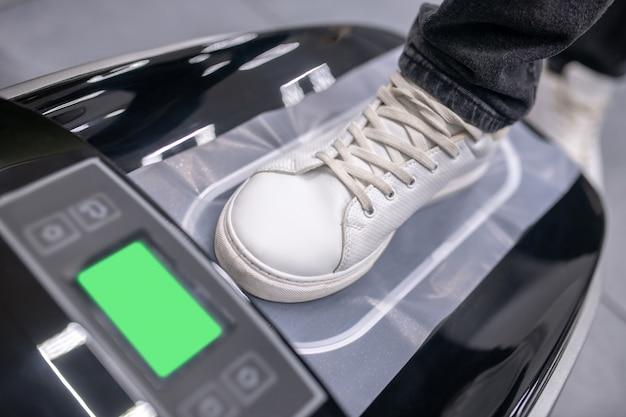 Nützliches gerät. bein im sneaker auf schwarzem elektronikgerät mit grünem kleinen monitor und thermofilm, der sich in deckung verwandelt