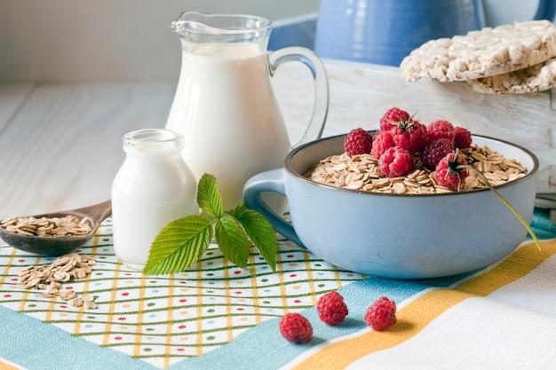 Nützliches hausgemachtes frühstück. haferflocken, milch und frische waldhimbeeren