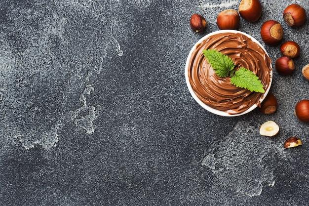 Nugatnussschokolade in einer platte auf einem dunklen konkreten hintergrund mit haselnussnüssen. konzept des frühstücks. kopieren sie platz.