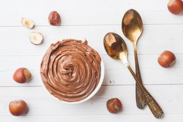 Nugatnussschokolade in einer platte auf einem weißen hintergrund mit haselnussnüssen. konzept des frühstücks.