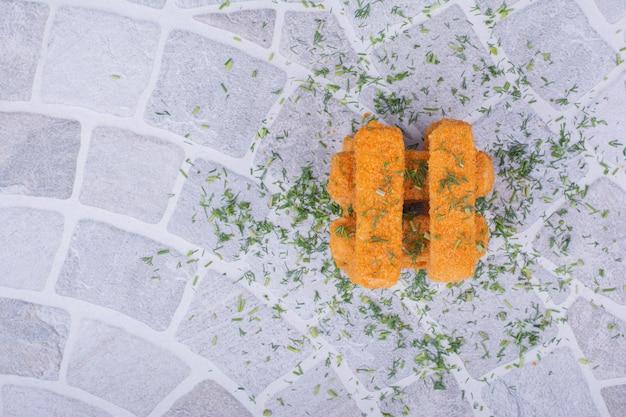 Nuggets mit kräutern und gewürzen auf grauer oberfläche