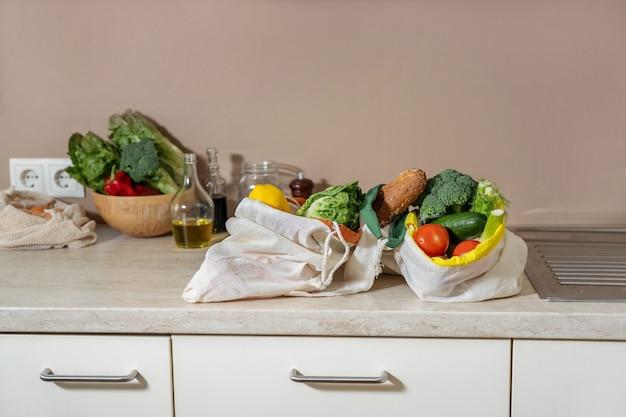 Null abfall baumwolltaschen mit lebensmitteln auf küchentisch. veganes naturkostkonzept. bio-essen aus der region. nachhaltiger lebensstil