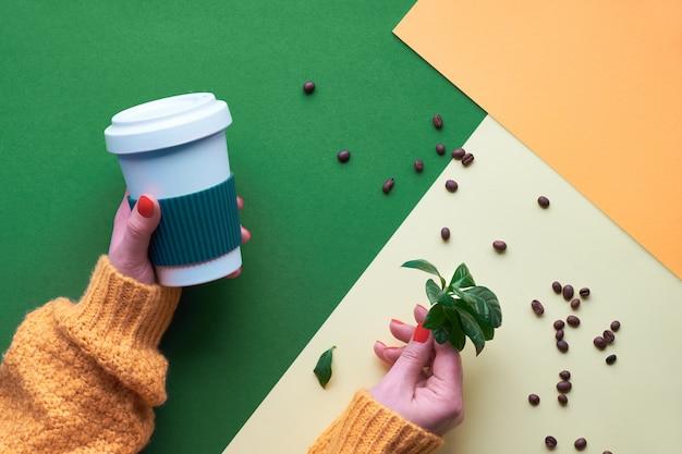 Null-abfall-kaffee-konzept. umweltfreundliche wiederverwendbare kaffeetassen in händen. die geometrische ebene lag auf geteiltem papier. kreative wand in den farben grün, orange und gelb.