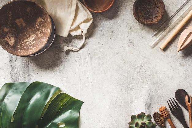 Null-abfall-konzept. kokosnussschüsseln, hölzernes tischbesteck, baumwolltaschen auf grauem hintergrund, kopienraum, draufsicht.
