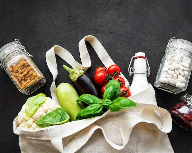 Null-abfall-konzept. öko-tasche mit obst und gemüse, gläser mit bohnen, nudeln. umweltfreundliches einkaufs- und kochkonzept, flachgelegt