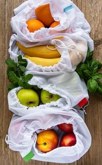 Null-abfall-konzept. öko-taschen mit früchten. umweltfreundliches einkaufs- und kochkonzept, flachgelegt