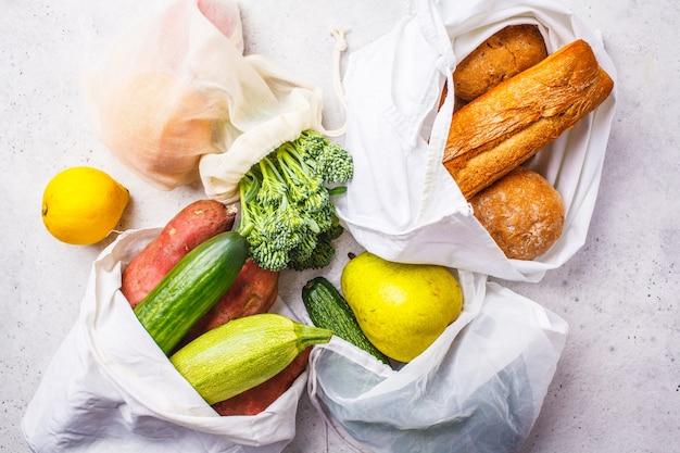 Null-abfall-konzept. öko-taschen mit obst und gemüse, umweltfreundliche vegane flachlage, kunststofffrei