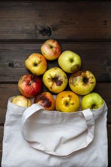 Null-abfall-konzept. rote und gelbe hässliche äpfel in der weißen textiltasche auf holztisch. äpfel auf dem tisch verstreut. von oben betrachten.