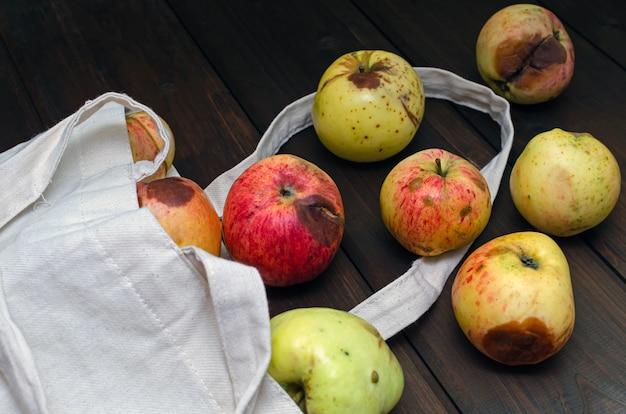 Null-abfall-konzept. rote und gelbe hässliche äpfel in der weißen textiltasche auf holztisch.