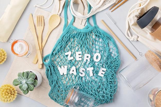 Null-abfall-konzept. set aus umweltfreundlichem bambusbesteck, mesh-baumwolltasche und wiederverwendbarem kaffeebecher. nachhaltiges, ethisches einkaufen, plastikfreier lebensstil. draufsicht, flach liegen.
