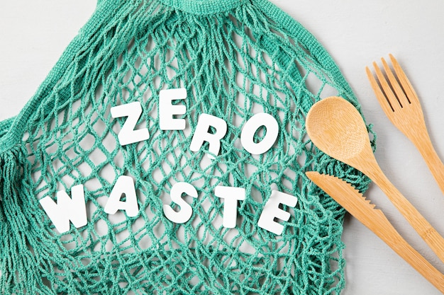 Null-abfall-konzept. set aus umweltfreundlichem bambusbesteck, mesh-baumwolltasche und wiederverwendbarem kaffeebecher. nachhaltiges, ethisches einkaufen, plastikfreier lebensstil. draufsicht, flach liegen. Premium Fotos