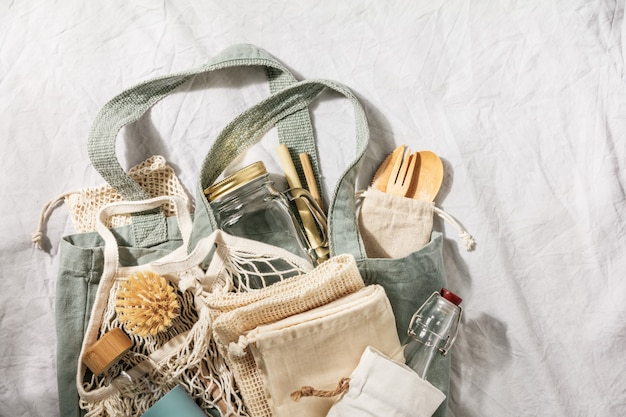 Null-abfall-konzept. textile öko-taschen, gläser, recyceltes bambusgeschirr auf leinenhintergrund