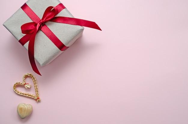 Null-abfall-konzept. umweltfreundliche hölzerne, weidenherzen und geschenk mit band auf einem rosa hintergrund. herzlichen glückwunsch zum valentinstag, geburtstag oder anderen feiertagen. horizontale ausrichtung