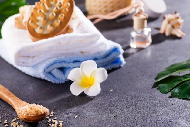 Null-abfall-konzept. umweltfreundliches badset. mit bürsten, meersalz, handtuch, aroma in glasflasche, bast und palmblättern