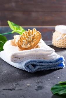 Null-abfall-konzept. umweltfreundliches badset mit bürsten und handtuch, aroma in glasflasche, bast und palmblättern