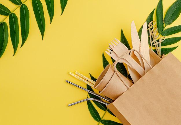 Null abfall mit bambus, einweggeschirr aus papier und metallstrohhalmen auf gelb