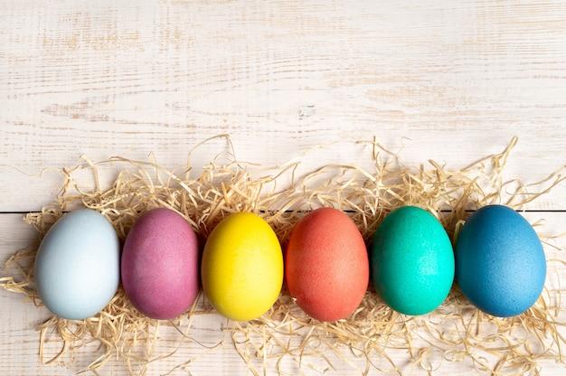 Null abfall ostern konzept. bunte eier auf weißem hölzernem hintergrund mit kopienraum für text. ansicht von oben nach unten oder flach legen