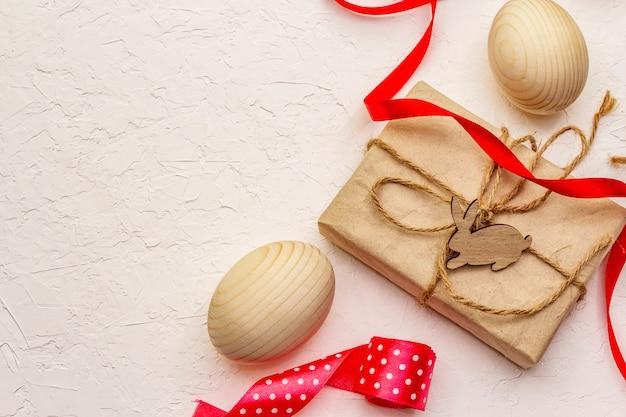 Null abfall ostern konzept. holzeier, geschenke in bastelpapier. nicht plastik, öko-trend. weißer kitthintergrund