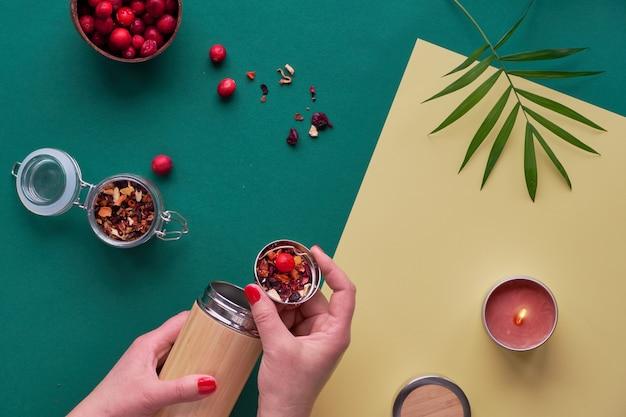 Null abfall tee zum mitnehmen, kräuteraufguss in umweltfreundlicher isolierter bambusstahlflasche mit kräutermischung und frischer cranberry. trendy kreative flache lage, draufsicht auf zweifarbigem grüngelbem papier.