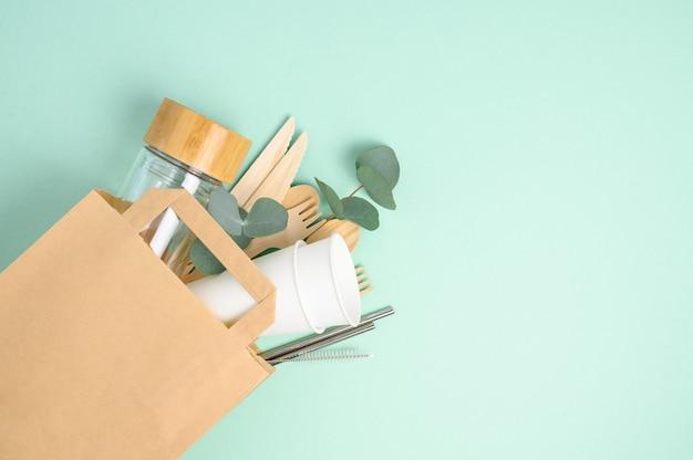 Null abfall und plastikfreies konzept. einkaufstüte mit glasflasche, tasse und blatt auf green.eco freundlichem modell.