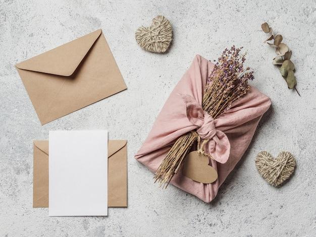 Null-abfall-valentinstag-konzept. umweltfreundlicher geschenkstoff, der in der furoshiki art, im kraftpapierumschlag, im leeren geschenk oder in der grußkarte, kopienraum einwickelt