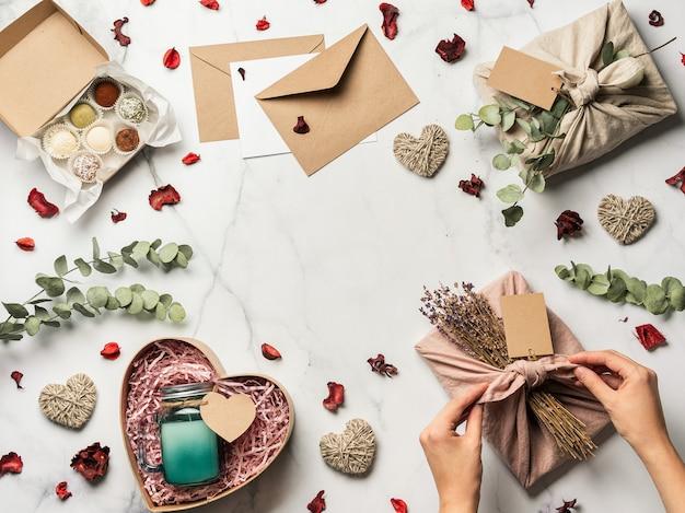 Null-abfall-valentinstag-konzept. umweltfreundlicher geschenkstoff, der in furoshiki-art, in selbst gemachten bonbons und in der kerze als geschenkideen auf weißem marmorhintergrund, kopienraum in der mitte einwickelt. draufsicht oder flachlage