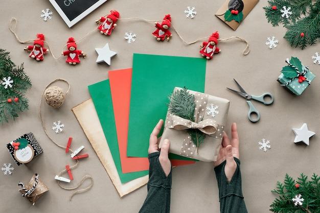 Null abfall weihnachten, flache lage, draufsicht auf bastelpapierwand mit roter puppengirlande, weibliche hände, die geschenk auf farbpapierstapel einwickeln. umweltfreundliche handgemachte weihnachtsdekorationen ohne kunststoff