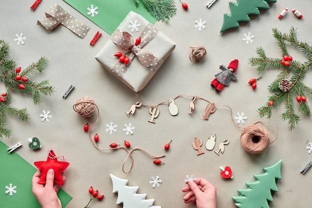 Null abfall weihnachten, konzept flaches layout auf rustikalem holz. handgefertigte geschenke, natürliche weihnachtsdekorationen aus biologisch abbaubaren materialien, kunststofffrei. flache lage, draufsicht, hände halten stern und puppe.