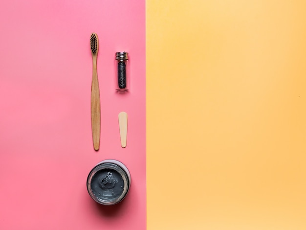 Null-abfall-zahnpflegekonzept. zahnbürste aus bambuskohle, zahnseide aus naturkohle und zahnpasta aus naturkohle in glas auf rosa hintergrund mit gelbem kopierraum rechts für text oder design